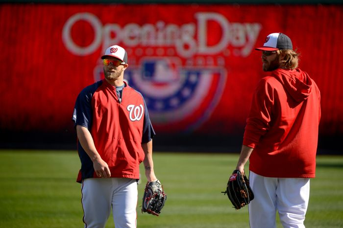 Washington Nationals left fielder Bryce Harper (34), left, and Washington Nationals right fielder Jayson Werth (28), right, warm up with the team before the Washington Nationals play the Miami Marlins on opening day at Nationals Park, Washington, D.C.,