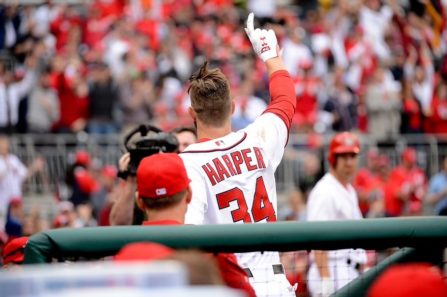Washington Nationals left fielder Bryce Harper (34) comes back out of the dugout to wave to fans after hitting his second home run of the game in the bottom of the 4th inning as the Washington Nationals play the Miami Marlins on opening day at Nationals Park, Washington, D.C., Monday, April 1, 2013. (Andrew Harnik/The Washington Times)