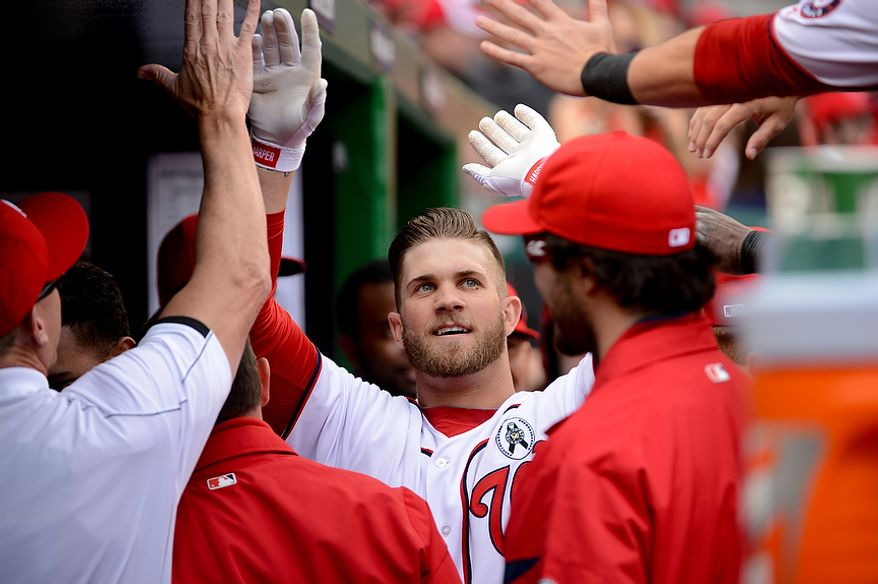 Washington Nationals left fielder Bryce Harper (34), center, gets high fives from teammates after hitting a solo home run in the first inning as the Washington Nationals play the Miami Marlins on opening day at Nationals Park, Washington, D.C., Monday, April 1, 2013. (Andrew Harnik/The Washington Times)