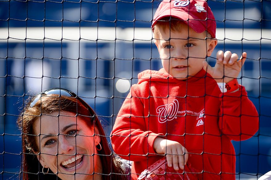 Kathy Nadherny and her son Jacob Thomas-Nadherny [cq], 3, of Arlington, Va. watch as the Washington Nationals warm up before they play the Miami Marlins on opening day at Nationals Park, Washington, D.C., Monday, April 1, 2013. (Andrew Harnik/The Washington Times)