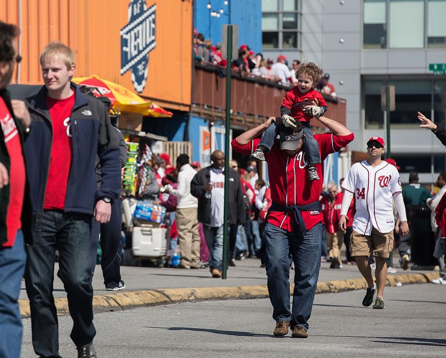Scott Burman, holds his son, Jack, on his shoulders as they make their way to the park to watch the Washington Nationals play the the Miami Marlins on opening day, at Nationals Park, in Washington, DC., Monday, April 1, 2013. (Andrew S Geraci/The Washington Times)