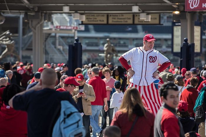 Mark Lohr, a stilt walker, greets fans as they enter the park to watch the Washington Nationals play the the Miami Marlins on opening day, at Nationals Pa