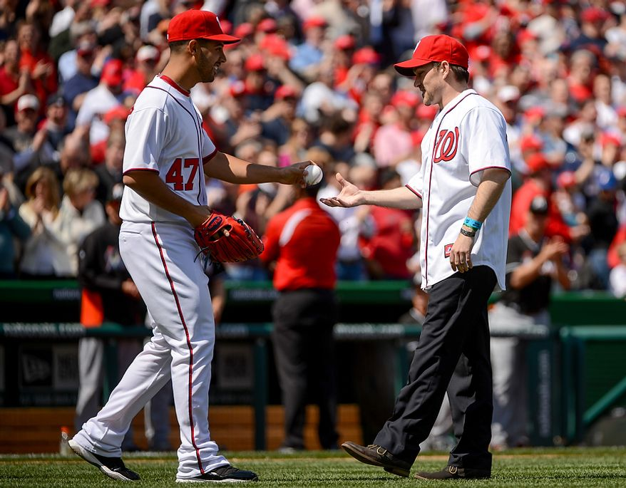 Metal of Honor recipient Clint Romesha is given a ball by Washington Nationals starting pitcher Gio Gonzalez (47) after throwing out the first pitch before the Washington Nationals play the Miami Marlins on opening day at Nationals Park, Washington, D.C., Monday, April 1, 2013. (Andrew Harnik/The Washington Times)