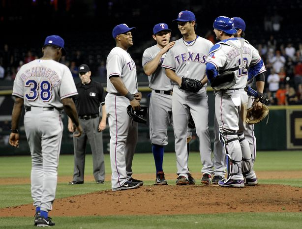 Texas Rangers' Yu Darvish, right center, is congratulated by teammates as manager Ron Washington heads out to the mound to pull him from the baseball game against the Houston Astros on Tuesday, April 2, 2013, in Houston. Darvish pitched eight and two-thirds perfect innings before giving up a hit to Astros' Marwin Gonzalez in the Rangers' 7-0 win. (AP Photo/Pat Sullivan)