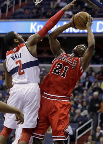 Chicago Bulls forward Jimmy Butler (21) shoots in front of Washington Wizards guard John Wall (2) in the first half of an NBA basketball game Tuesday, April 2, 2013, in Washington. (AP Photo/Alex Brandon)