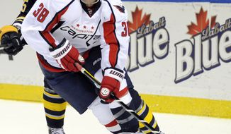 Buffalo Sabres center Brian Flynn (65) gives chase to Washington Capitals defenseman Jack Hillen (38) during the first period of an NHL hockey game in Buffalo, N.Y., Saturday, March 30, 2013. (AP Photo/Gary Wiepert)