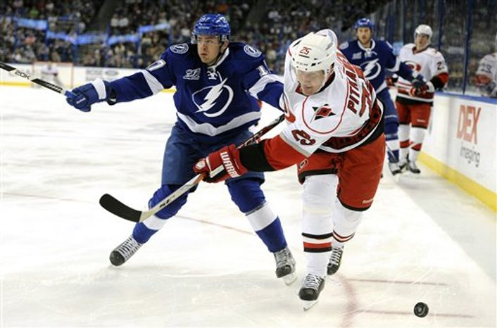 Carolina Hurricanes defenseman Joni Pitkanen, of Finland, and Tampa Bay Lightning center Alex Killorn, left, go for the puck during the first period of an NHL hockey game Saturday, March 16, 2013, in Tampa, Fla. (AP Photo/Brian Blanco)