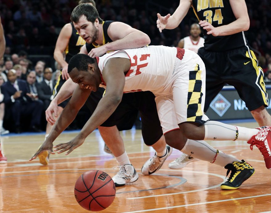 Iowa's Zach McCabe (15) and Maryland's Charles Mitchell (0) fight for control of the ball during the first half of an NIT semifinal basketball game Tuesday, April 2, 2013, in New York. (AP Photo/Frank Franklin)