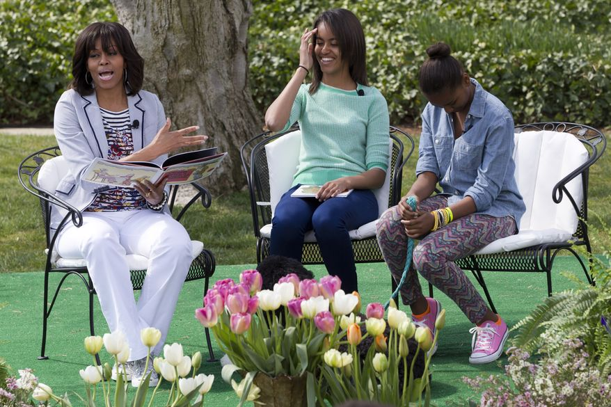 First lady Michelle Obama (left), with daughters Malia (center) and Sasha, reads a book to children during the annual Easter Egg Roll on the South Lawn of the White House in Washington on Monday, April 1, 2013. (AP Photo/Jacquelyn Martin)