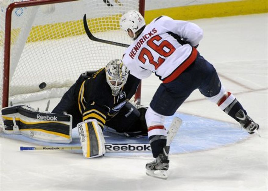 Buffalo Sabres' goaltender Jhonas Enroth (1), of Sweden, gets beat for goal by Washington Capitals' center Matt Hendricks (26) during the team shootout of an NHL hockey game in Buffalo, N.Y., Saturday, March 30, 2013. Washington won 4-3. (AP Photo/Gary Wiepert)