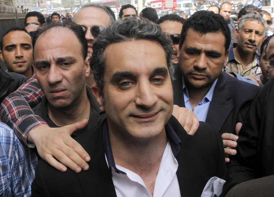 ** FILE ** In this Sunday, March 31, 2013, file photo, a bodyguard secures popular Egyptian television satirist Bassem Youssef, who has come to be known as Egypt's Jon Stewart, as he enters Egypt's state prosecutors office to face accusations of insulting Islam and the country's Islamist leader in Cairo, Egypt. (AP Photo/Amr Nabil, File)