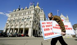 Jody Winslow, of Farmington, Conn., carries signs referencing the Second Amendment near the Capitol where gun rights advocates were gathering as lawmakers voted on a gun control bill, four months after the Newtown shootings.