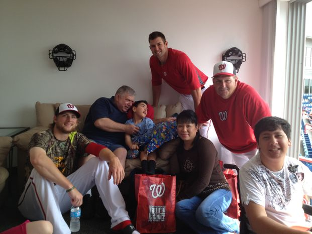 Nationals pitchers Ross Detwiler, left, Craig Stammen, top right, and third base coach Trent Jewett, right, visit with children and parents from Wheelchairs 4 Kids before a spring training game in Viera, Fla. (Photo courtesy of Wheelchairs 4 Kids)