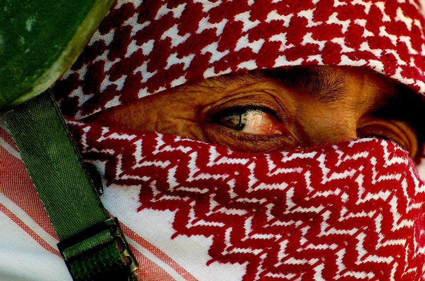 Iraqi policemen wrap their faces with scarves to conceal their identity before heading out on patrols from Al Huriya Police Station in Ramadi, Iraq, July 27, 2006. (U.S. Air Force photo by Tech. Sgt. Jeremy T. Lock)