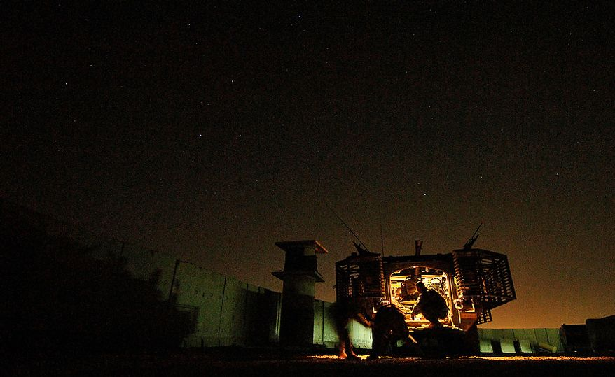 U.S. Army Soldiers try to pull an illumination flare from it's case before firing it over the city of Mosul, Iraq, June 1, 2006, with a 120mm mortar cannon. The illumination flares are fired will brighten the city to deter terrorist from planting improvised explosive devices. The Soldiers are from Headquarters and Headquarters Company, 1st Battalion, 17th Battalion Mortars, 172nd Stryker Brigade Combat Team. (U.S. Air Force photo by Tech. Sgt. Jeremy T. Lock)
