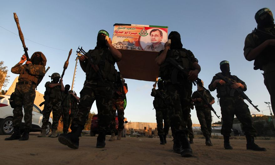 Izzedine Al-Qassam Brigades militants carry a mock coffin of Maysara Abu Hamdiyeh in the Gaza Strip on Tuesday, April 2, 2013. Abu Hamdiyeh, 64, who was serving a life sentence for his role in a foiled attempt to bomb a busy cafe in Jerusalem in 2002, died Tuesday of cancer in an Israeli jail. (AP Photo/Hatem Moussa)