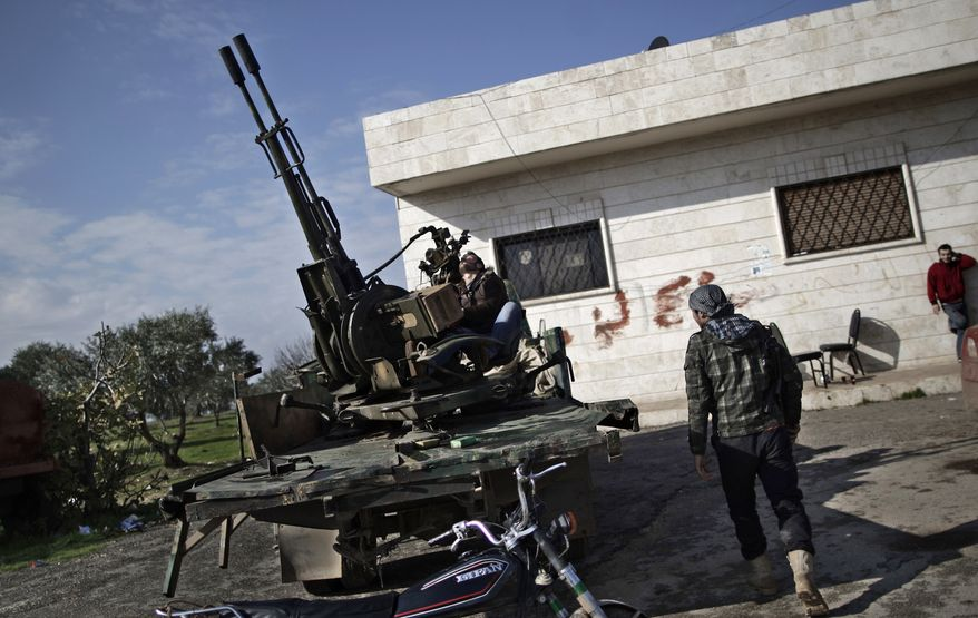 ** FILE ** In this Friday, Dec. 14, 2012, file photo, a Syrian rebel checks an anti-aircraft weapon, in Maaret Misreen, near Idlib, Syria. (AP Photo/Muhammed Muheisen, File)