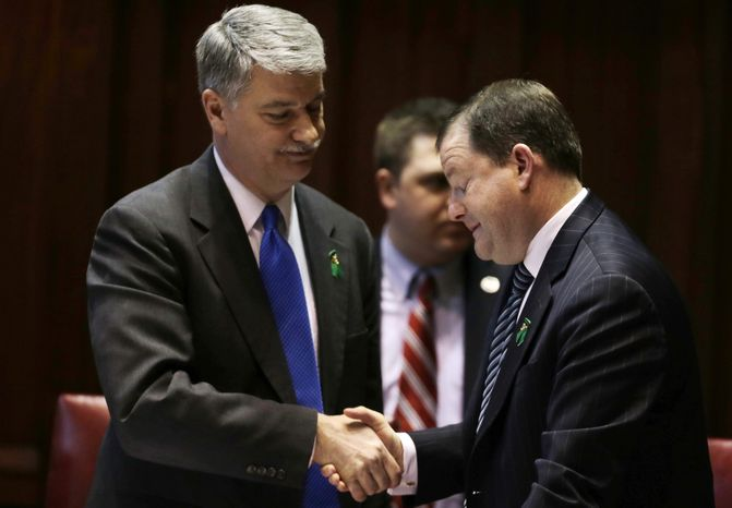 Senate Minority Leader John McKinney, R-Fairfield, who represents Newtown, Conn., right, and Senate President Donald Williams, D-Brooklyn, shake hands after the passage of a gun-control bill in the Senate chamber at the Capitol in Hartford, Conn., Wednesday, April 3,