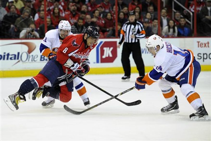 Washington Capitals left wing Alex Ovechkin (8), of Russia, battles for the puck against New York Islanders defenseman Lubomir Visnovsky (11), of Slovakia, and Thomas Hickey, right, during the first period of an NHL hockey game on Thursday, April 4, 2013, in Washington. (AP Photo/Nick Wass)
