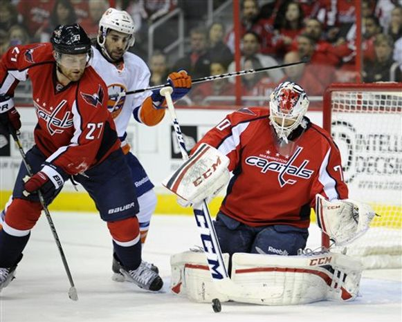Washington Capitals goalie Braden Holtby (70) stops the puck against New York Islanders left wing Matt Moulson, center, during the second period of an NHL hockey game on Thursday, April 4, 2013, in Washington. Capitals defenseman Karl Alzner (27) looks on. (AP Photo/Nick Wass)