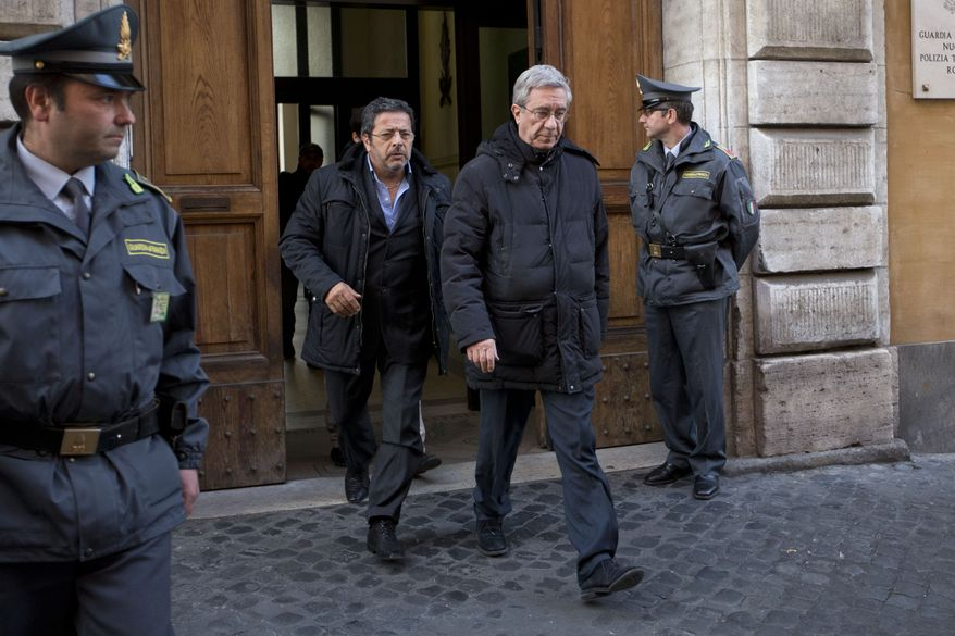 The Rev. Franco Decaminada (second from right) leaves an office of Italy's financial police after being questioned in Rome on Thursday, April 4, 2013. The Catholic priest, who is under house arrest, is accused of pocketing 4 million euros ($5.1 million) from the coffers of a Catholic hospital he ran and helping run up 600 million euros ($769 million) in debts that forced the clinic into bankruptcy and prompted the Vatican to intervene. (AP Photo/Andrew Medichini)
