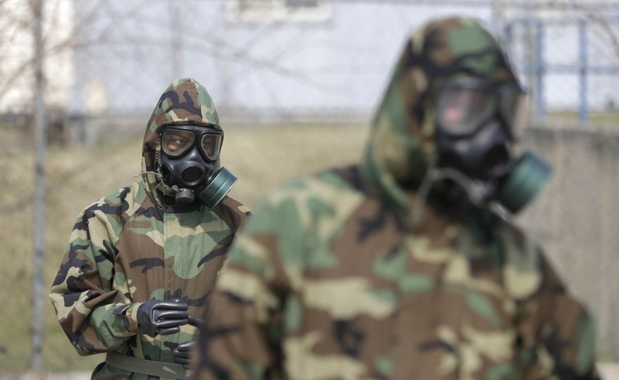 Soldiers of the U.S. Army 23rd chemical battalion wear gas masks while attending a demonstration of their equipment during a ceremony to recognize the battalion's official return to the 2nd Infantry Division based in South Korea at Camp Stanley in Uijeongbu, north of Seoul, Thursday, April 4, 2013. The 23rd chemical battalion left South Korea in 2004 and returned with some 350 soldiers in Jan. 2013. (AP Photo/Lee Jin-man)