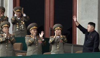**FILE** North Korean leader Kim Jong-un (left) waves April 14, 2012, as North Korean military officers clap at a stadium in Pyongyang during a mass meeting called by the Central Committee of North Korea's ruling party. (Associated Press)
