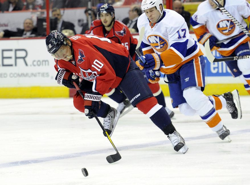 Washington Capitals left wing Martin Erat (10), of the Czech Republic, chases the puck against New York Islanders left wing Matt Martin (17) during the second period of an NHL hockey game on Thursday, April 4, 2013, in Washington. (AP Photo/Nick Wass)