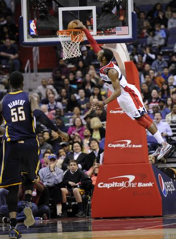 Washington Wizards guard John Wall (2) goes up for a dunk as Indiana Pacers center Roy Hibbert (55) looks on during the first half of an N