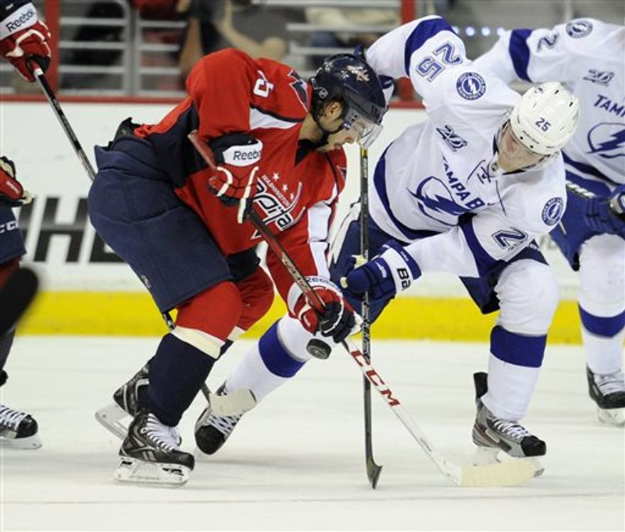 Tampa Bay Lightning defenseman Matt Carle (25) battles for the puck against Washington Capitals center Mathieu Perreault (85) during the first period of an NHL hockey game, Sunday, April 7, 2013, in Washington. (AP Photo/Nick Wass)