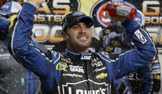Jimmie Johnson celebrates after winning the STP 500 NASCAR Sprint Cup series auto race at Martinsville Speedway in Martinsville, Va., Sunday, April 7, 2013. (AP Photo/Steve Helber)