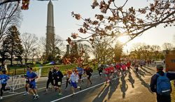 Warmer weather greeted participants in the Cherry Blossom Ten Mile run Sunday, though there still was a chill in the air when it kicked off at 7:30 a.m. Some got close to get warm while members of the Hash Club handed out beers on the National Mall as the cherry blossoms tried to make an appearance. (Andrew Harnik/The Washington Times)