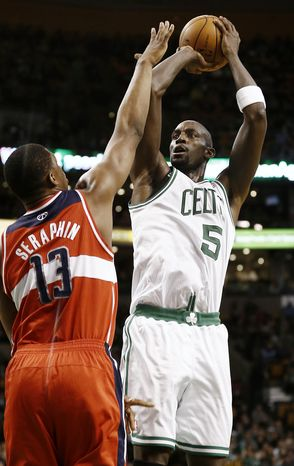 Boston Celtics' Kevin Garnett, right, shoots over Washington Wizards' Kevin Seraphin during the second quarter of an NBA basketball game in Boston, Sunday, April 7, 2013. (AP Photo/Winslow Townson)