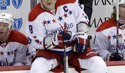 Washington Capitals left wing Alex Ovechkin sits on the boards in front of his bench with coach Adam Oates behind him during a first-period timeout in an NHL hockey game against the Pittsburgh Penguins in Pittsburgh on Tuesday, March 19, 2013. The Penguins won 2-1. (AP Photo/Gene J. Puskar)