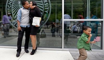 **FILE** New U.S. citizen Johanna Cornielle Mesa of Lawrence, Mass., originally from the Dominican Republic, gets a kiss from her boyfriend, Luis, while their son Luis Jr. plays with a flag after a naturalization ceremony in Fitchburg, Mass., on Sept. 6, 2012. (Associated Press)