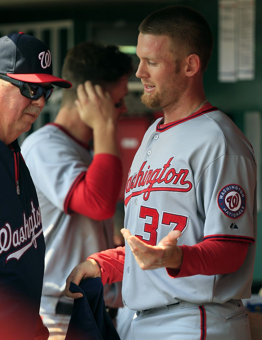Washington Nationals pitcher Stephen Strasburg talks with pitching coach Steve McCatty after the forth inning as they play against the Cincinnati Reds during their baseball game in Cincinnati Sunday April 7, 2013. (AP Photo/Tom Uhlman)