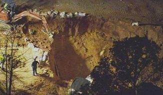 ** FILE ** In this image made from video and provided by WSOC-TV Charlotte, authorities work to rescue two children at a construction site, Sunday, April 7, 2013, in Stanley, N.C. (AP Photo/WSOC TV)
