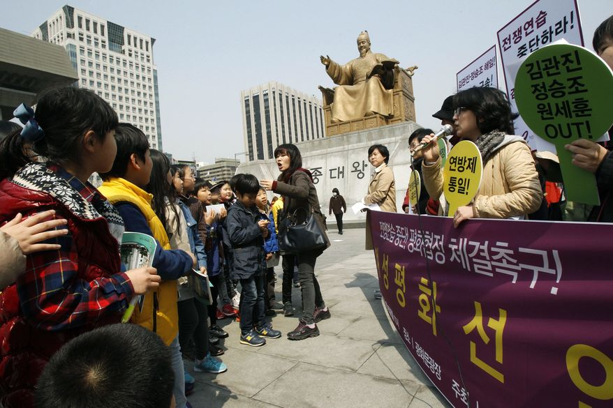 An unidentified elementary school teacher, center, orders her students to leave as they watch South Korean housewives stage a press conference denouncing the annual joint military exercise known as Foal Eagle, between South Korea and the United States, near the U.S. Embassy in Seoul, South Korea, Monday, April 8, 2013. (AP Photo/Ahn Young-joon)
