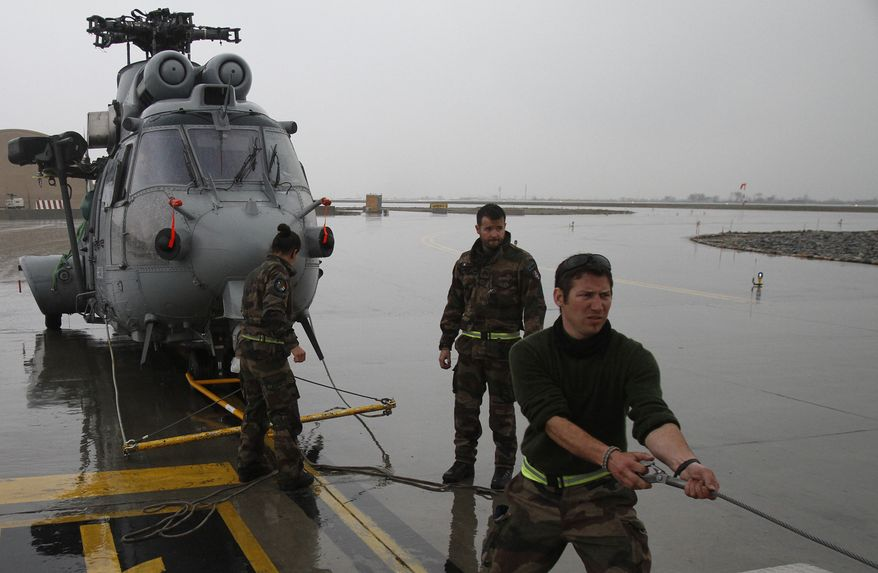 ** FILE ** French soldiers prepare to load a helicopter into a cargo aircraft to ship it back home to France, at Kabul military airport in Kabul, Afghanistan, Tuesday, March 12, 2013. (AP Photo/Ahmad Jamshid)
