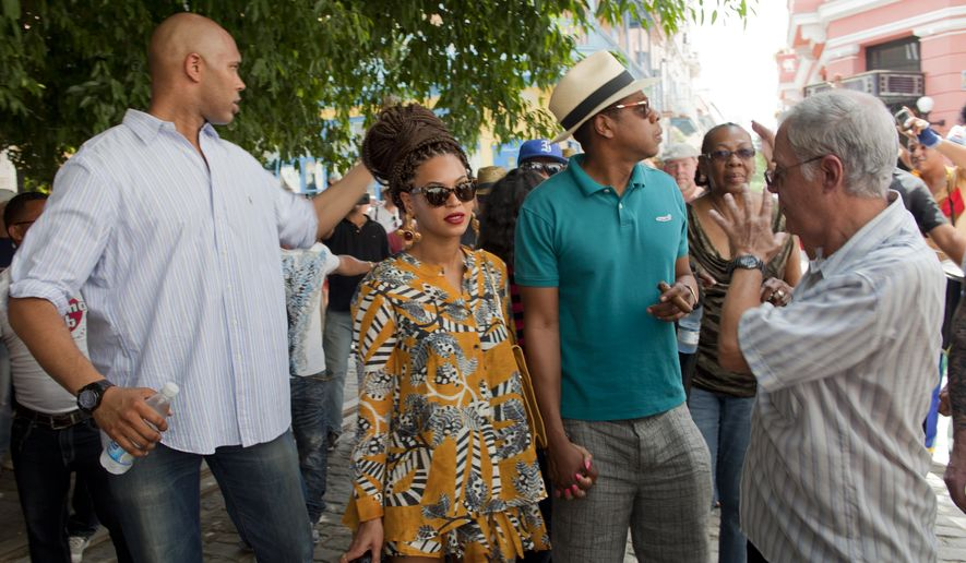 ** FILE ** U.S. singer Beyonce and her husband, rapper Jay-Z, right, tour Old Havana as a body guard, left, and tour guide, right, accompany them in Cuba, Thursday, April 4, 2013. R&B power couple is in Havana on their fifth wedding anniversary. (AP Photo/Ramon Espinosa)