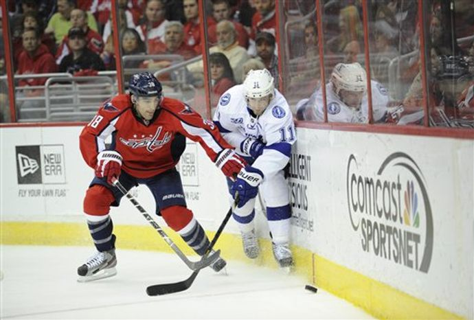 Washington Capitals defenseman Jack Hillen (38) battles for the puck against Tampa Bay Lightning center Tom Pyatt (11) during the second period of an NHL hockey game, Sunday, April 7, 2013, in Washington. (AP Photo/Nick Wass)