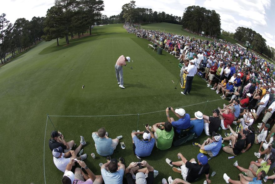 In a photo taken with a fisheye lens, Tiger Woods tees off on the third hole during a practice round for the Masters golf tournament Tuesday, April 9, 2013, in Augusta, Ga. (AP Photo/Charlie Riedel)