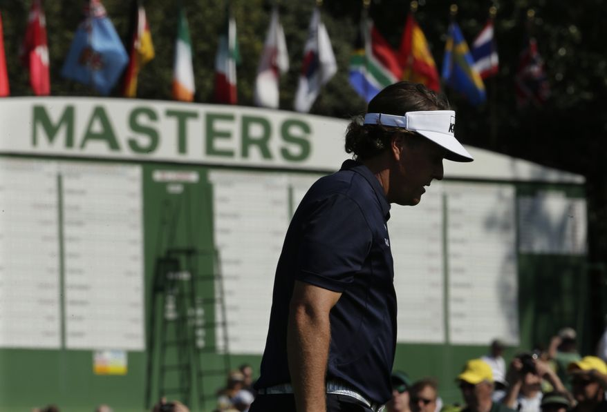 Phil Mickelson walks past a scoreboard while walking up the ninth hole during a practice round for the Masters golf tournament Tuesday, April 9, 2013, in Augusta, Ga. (AP Photo/Charlie Riedel)