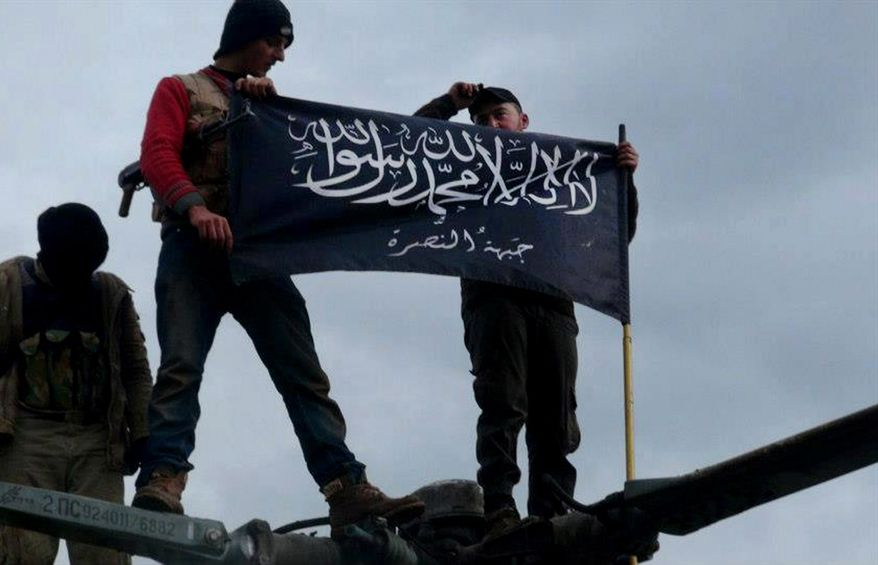 **FILE** In this citizen journalism image provided by Edlib News Network, which has been authenticated based on its contents and other AP reporting, rebels from al Qaeda-affiliated Jabhat al-Nusra wave their brigade flag on the top of a Syrian air force helicopter on Jan. 11, 2013, at the Taftanaz air base in the Idlib province of northern Syria that was captured by the rebels. (Associated Press/Edlib News Network)