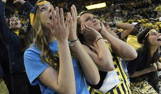 Michigan Juniors Janna Kramer, left, and Anna Paneral watch the final moments of the game at Crisler Arena in Ann Arbor as Michigan falls to Louisville 82-76 in the NCAA final in Atlanta, Monday April 8, 2013. (Associated Press)