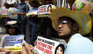 Protesters display placards as they picket the Presidential Commission on Good Government (PCGG), a government body tasked with recovering alleged ill-gotten wealth of the late deposed strongman Ferdinand Marcos, on Monday, April 8, 2013, at Mandaluyong, Philippines, northeast of Manila. (AP Photo/Bullit Marquez)