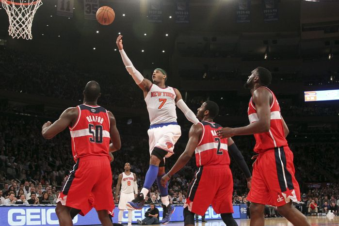 New York Knicks' Carmelo Anthony (7) goes up past Washington Wizards' Emeka Okafor (50) John Wall and Chris Singleton during the second half of n NBA basketball game, Tuesday, April 9, 2013, at Madison Square Garden in