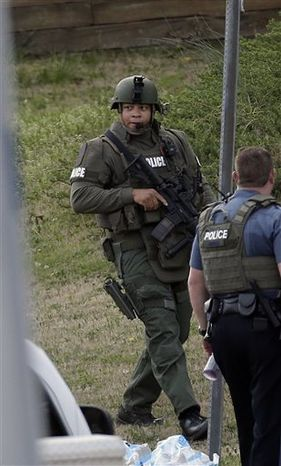 A police officer holds a rifle as he walks near the scene where a man is said to be holding four Gwinnett County firefighters hostage in Suwanee, Ga., Wednesday, April 10, 2013. (AP Photo/John Bazemore)