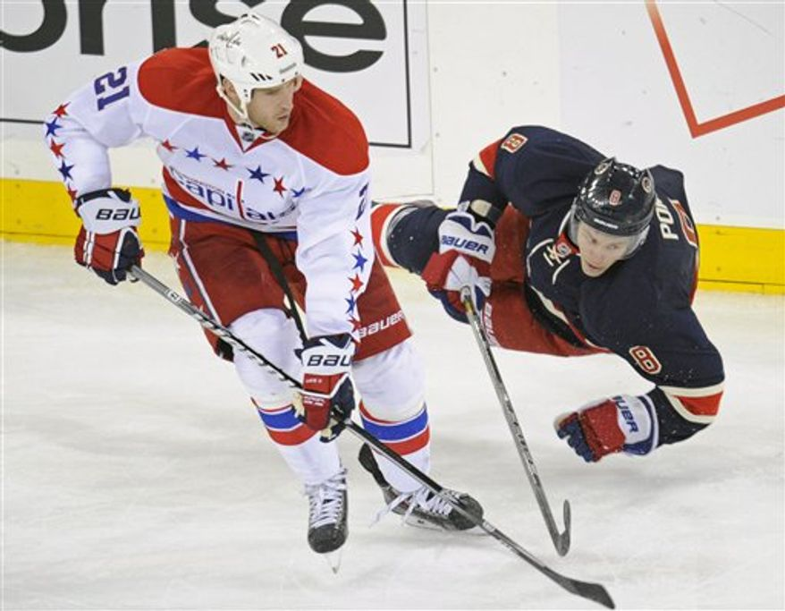 Washington Capitals' Brooks Laich, left, checks New York Rangers' Darroll Powe during the third period of an NHL hockey game Sunday, March 24, 2013, at Madison Square Garden in New York. The Capitals won 3-2 in a shootout. (AP Photo/Bill Kostroun)