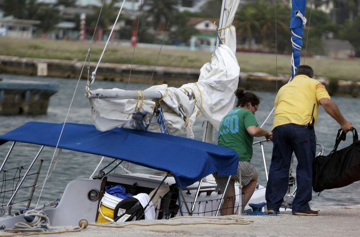 Sharyn Hakken is helped out of her boat by a safety officer at the Hemingway Marina in Havana, Cuba, Tuesday, April 9, 2013. Sharyn and her husband Joshua Michael Hakken, who had lost custody of their two young boys, allegedly kidnapped them from Sharyn's parents in Florida and fled by boat to Havana. (AP Photo/Franklin Reyes)
